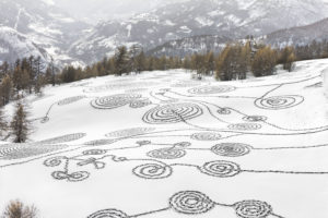 "'Snow Drawings – Briancon' was created by Sonja Hinrichsen in February 2014 in the Valley of Serre Chevalier – a skiing area in the French Alps. The piece wraps around a mountainside, stretching upward along a hiking trail/mountain road. The piece was created over two days with the help of approximately 70 participants from the surrounding communities who entered the ""snow canvas"" from different locations along the hiking trail to create the intricate designs. (Photo courtesy of the Shelburne Museum)"