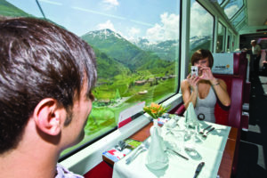 A couple enjoy a trip on the Glacier Express through the Swiss Alps. (Photo courtesy of the Glacier Express)