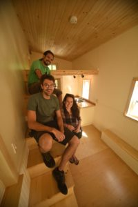 Bob Greel, Kate Ziegler and Anderson Page from Tiny House Crafters LLC, sit on the stairway/storage unit in one of the company's homes. (Contributed photo)